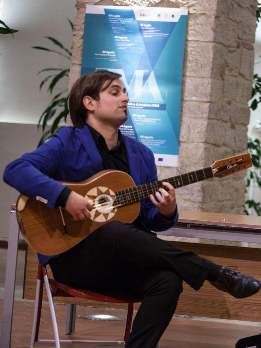 La posizione per suonare la chitarra battente con la gamba destra accavallata sulla sinistra