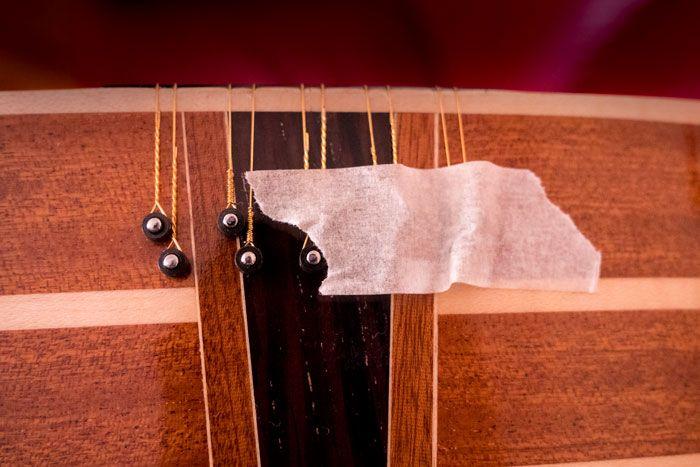 Corde per chitarra battente fissate alla fascia inferiore con nastro di carta per mascheratura per  cambiare le corde alla chitarra battente