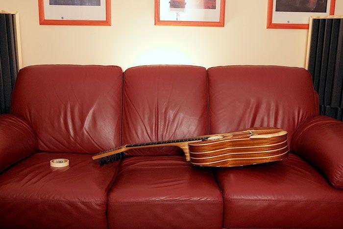 Chitarra battente sul divano per il cambio delle corde