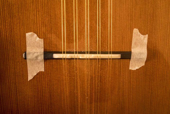 Il ponte della chitarra battente fissato con due strisce di nastro di carta per mascheratura per permettere il cambio delle corde in modo più agevole